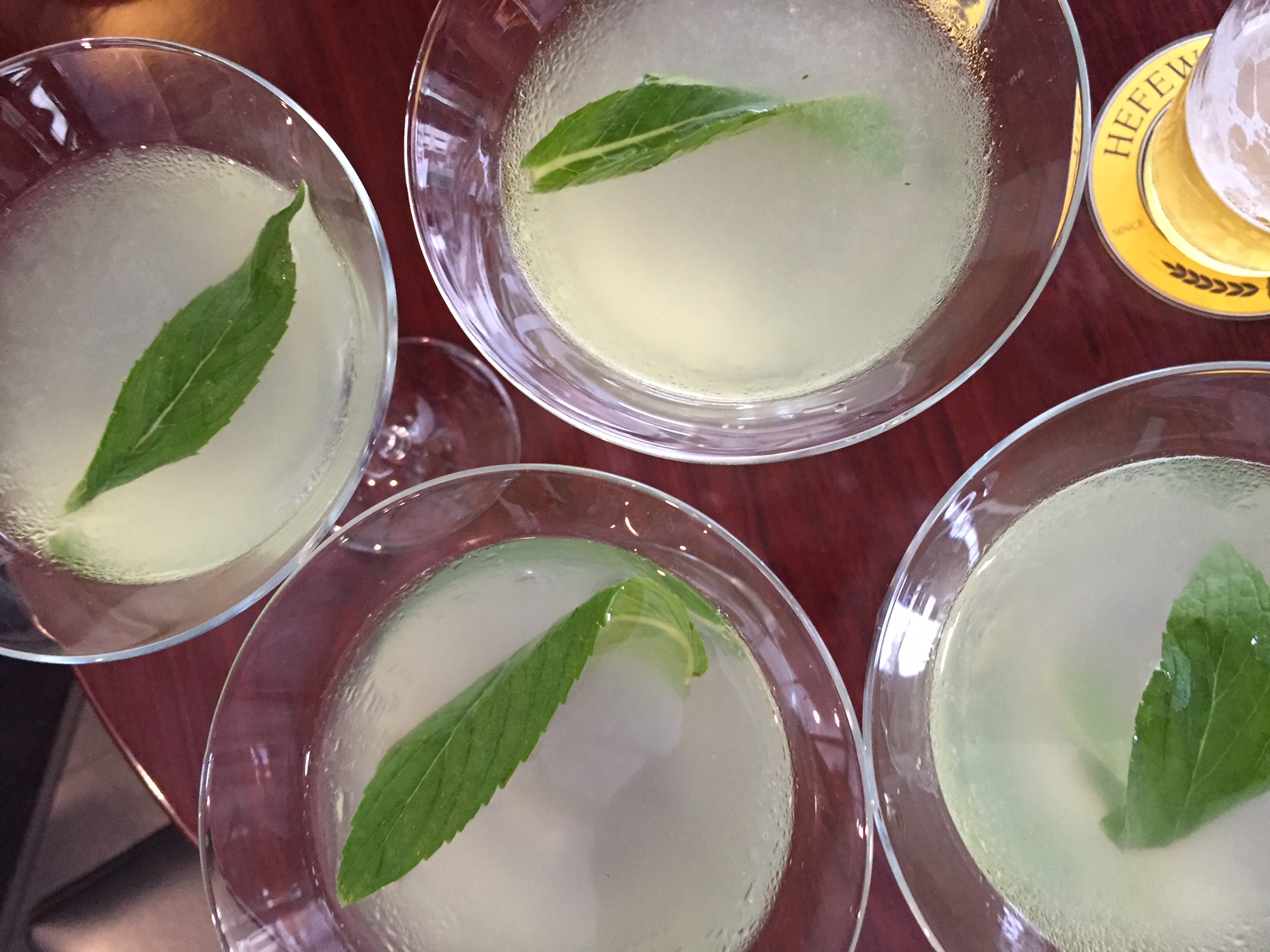 Four garnished cocktails poured in martini glasses