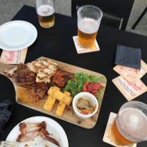 Bar table featuring wooden plate of ribs and cups of lager on the table.